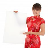 Asian woman with Chinese traditional dress cheongsam or qipao, holding blank white placard. Chinese