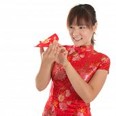 Asian woman with Chinese traditional dress cheongsam or qipao holding ang pow monetary gift, peeking
