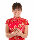 Pretty Asian woman with Chinese traditional dress cheongsam or qipao holding ang pow or red packet m