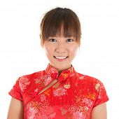 Asian woman with Chinese traditional dress cheongsam or qipao, close up face shot. Chinese new year
