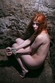 stock photo of catacombs  - redheaded nude woman bondage in catacomb - JPG