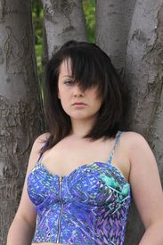 stock photo of halter-top  - Pretty teenager in a halter top leaning back against a tree trunk - JPG