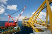 stock photo of barge  - Large crane vessel installing the platform in offshore,crane barge doing marine heavy lift installation works in the gulf or the sea