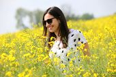 Girl in the meadow full of yellow flowers