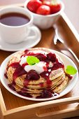 pancakes with cherry jam and cream for breakfast