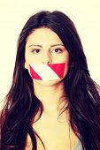 Freedom of speech concept. Young beautiful woman with red and white tape on her mouth. Isolated on w