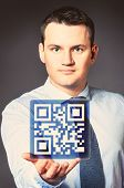 caucasian businessman is holding qr code in hands