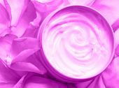 cosmetic cream surrounded by rose petals