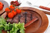 lunch of fresh rich juicy grilled beef meat steak fillet with marks on wooden plate over white table