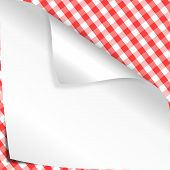 Bent corner of white paper on checkered tablecloth