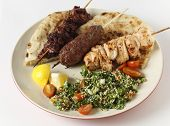 Various barbecued kebabs - kofta, chicken tawook and sumac chicken - with tabouleh and pitta bread; an Arab or Lebanese-style feast.