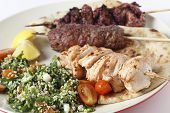 Various barbecued kebabs - kofta, chicken tawook and sumac chicken - with tabouleh and pitta bread;