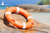 Orange lifebuoy on rocks at sea side. lifesaving equipment. concept