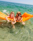 Three kids enjoying summer day floating in the sea