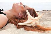 Beautiful Girl Lies On Sea Coast With Shells