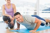 Portrait of handsome man doing push ups with female trainer in fitness studio