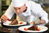 image of pastry chef  - Closeup of a concentrated male pastry chef decorating dessert in the kitchen - JPG