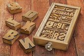 letterpress wood type blocks in a typesetter drawer against rustic red barn wood