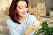 Smiling woman using smartphone at home