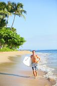 Beach lifestyle man surfer with surfing bodyboard running in water on tropical beach. Handsome male