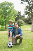 Full length portrait of a father and son with ball at the park