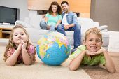 Smiling siblings lying on the rug with a globe at home in living room