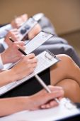 stock photo of person writing  - Row of business people writing lecture at seminar - JPG