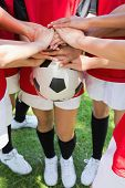 Cropped image of female soccer team stacking hands on ball at park