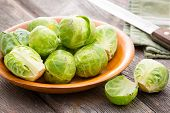 picture of cruciferous  - Bowl of fresh uncooked cleaned brussels sprouts with one halved one in the foreground standing on an old rustic wooden kitchen table alongside a knife - JPG