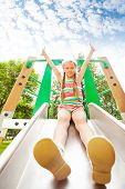Girl with hands up sits on playground chute
