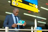 smiling african american businessman checking his flight ticket at airport