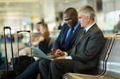 successful business travelers using laptop at airport