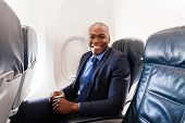 cheerful afro american businessman on board of an airplane during the flight