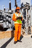 happy afro american electrical engineer with clipboard in power plant