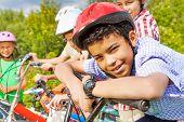 Smiling boy in helmet holds handle-bar of bike