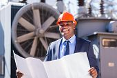 stock photo of substation  - cheerful young african electrical manager holding blueprint in electric substation - JPG