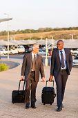 smart businessmen walking in airport parking lot