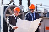 power plant managers holding blueprint at substation