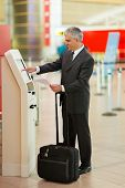 middle aged businessman using self help check in machine at airport