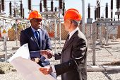 foto of substation  - friendly business partners handshaking in electrical substation - JPG