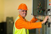 happy mid age electrician checking industrial control box