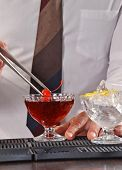 Barman preparing cocktail drink and cherry.