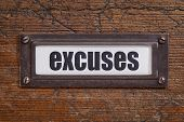 excuses  - file cabinet label, bronze holder against grunge and scratched wood