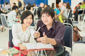 Thai (asian) Business Copule Are Showing Success Gesture In The Work Project