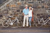 Happy senior couple going for a bike ride in the city on a sunny day