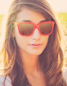Portrait of young beautiful woman in hipster sun glasses outside, bright sunny warm color tones