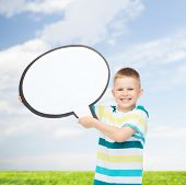 happiness, childhood, conversation, environment and people concept - smiling little boy with blank text bubble over natural background