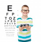 vision, health, ophthalmology and people concept - smiling little boy in eyeglasses holding spectacl