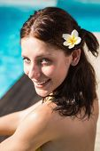 Portrait of a beautiful young woman by swimming pool on a sunny day