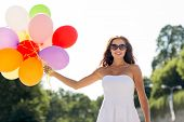 happiness, summer, holidays and people concept - smiling young woman wearing sunglasses with balloon